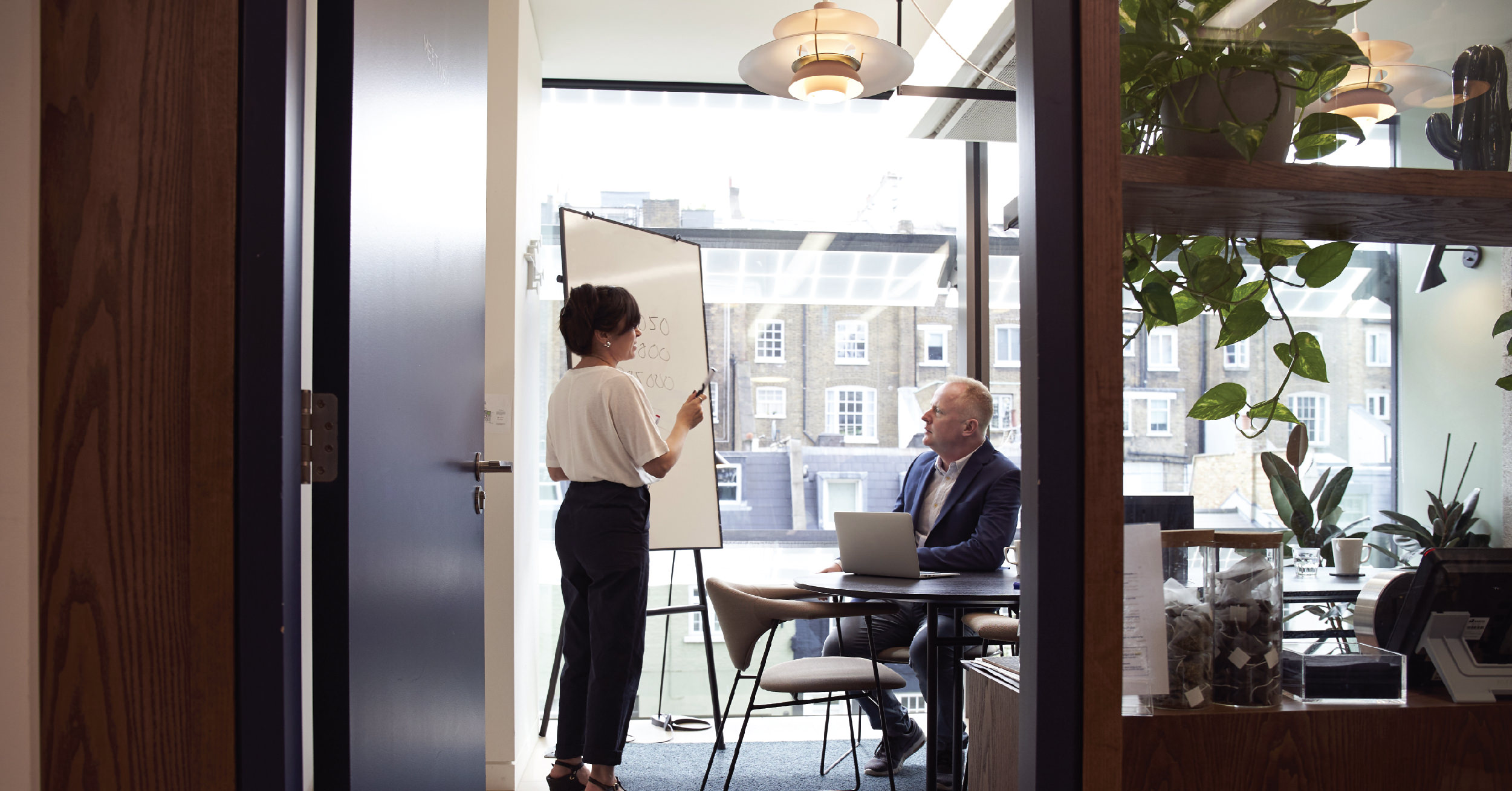 Assertive woman presenting to a man in a meeting room with a whiteboard
